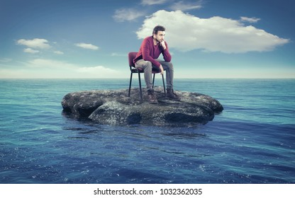 Thoughtful man on a chair in the middle of the ocean