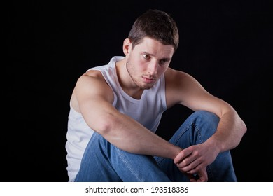 Thoughtful man on isolated black background, horizontal