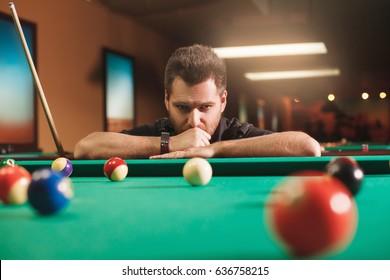 Thoughtful man plays billiards. Billiard room on the background.