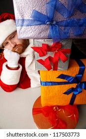 Thoughtful man in Santa costume is looking at  heap of presents