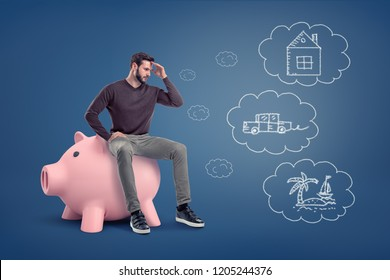 A thoughtful man sits on a large piggy bank near chalk drawings of a house, a car and an island. Choosing how to spend money . Savings and investments. Budget decisions.