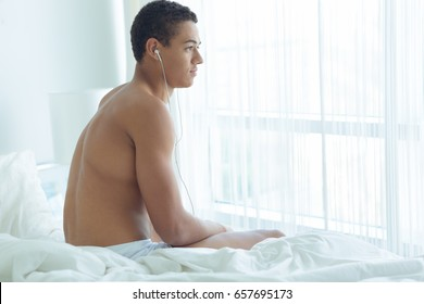 Thoughtful man sitting in bed and listening to music with headphones in the morning.