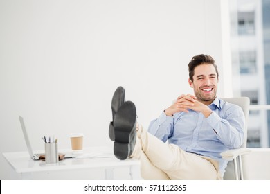 Thoughtful man sitting with feet on table in office