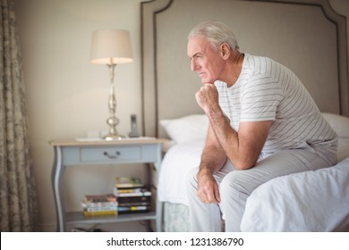 Thoughtful man sitting on bed in bedroom at home