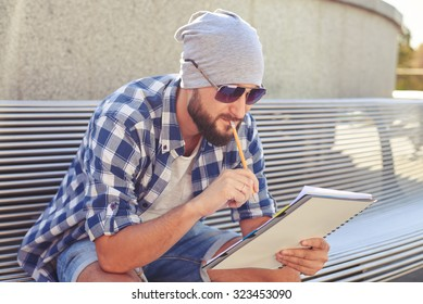 thoughtful man sitting on bench and looking at his notepad at outdoors