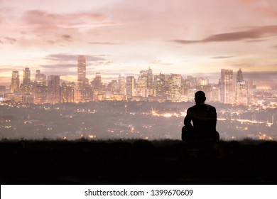 Thoughtful man sitting on a hill looking at the city skyline.