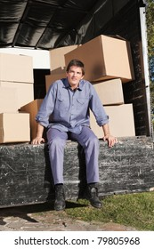 Thoughtful man sitting in the truck with pile of boxes behind him