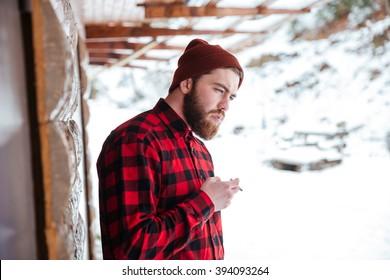 Thoughtful man smoking cigarette outdoors