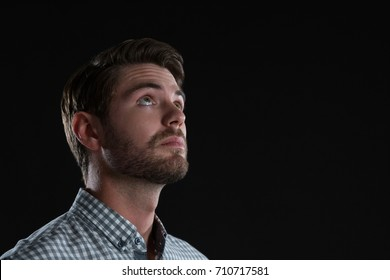 Thoughtful man standing against black background
