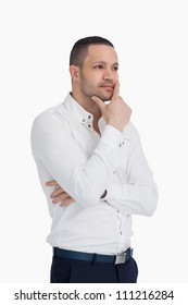 Thoughtful man standing and crossing his arms against a white background