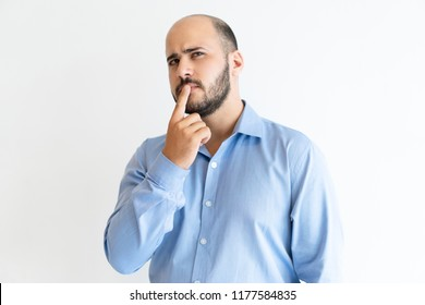 Thoughtful man touching mouth with finger and looking away. Handsome guy thinking. Contemplation concept. Isolated view on white background.