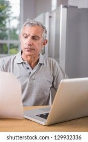 Thoughtful man using his laptop and reading a file at home