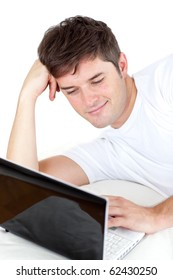 Thoughtful man using his laptop lying on the ground against a white background