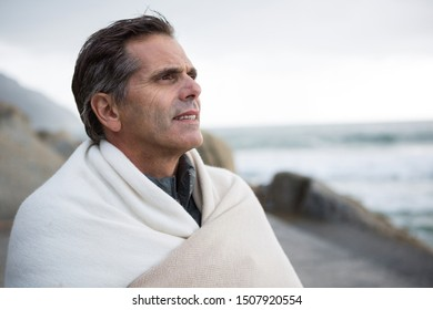 Thoughtful man wrapped in shawl on beach during winter