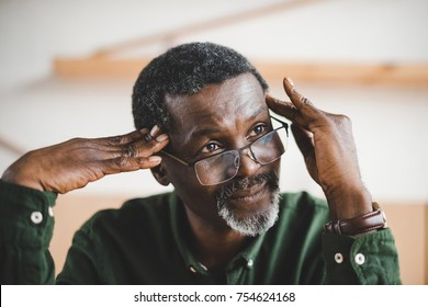 thoughtful mature african american man looking away and touching head