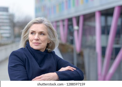 Thoughtful mature attractive blond woman looking back over her shoulder watching as she stands leaning on the edge railing of an urban exterior walkway