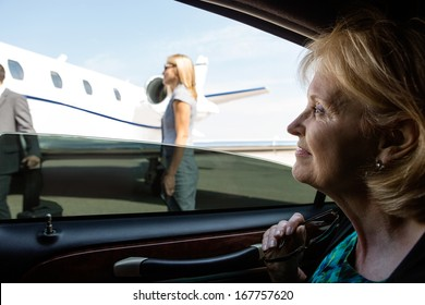 Thoughtful mature businesswoman in car looking at private jet