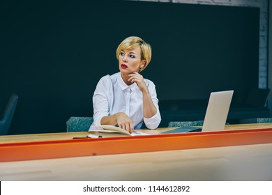 Thoughtful mature businesswoman looking away and thinking on analyzing project sitting at modern laptop computer in office.Contemplative female professor pondering on ideas working at netbook