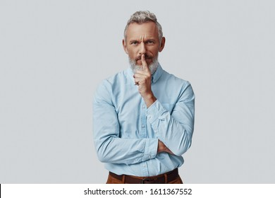 Thoughtful mature man looking at camera and keeping finger on lips while standing against grey background