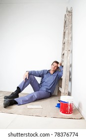 Thoughtful mature man sitting on floor with paint bucket beside
