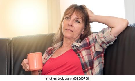 Thoughtful mature woman sitting on sofa, light effect