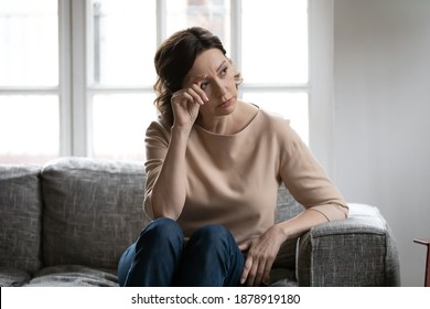 Thoughtful mature woman touching forehead, lost in thoughts, memories, sitting on couch at home alone, upset pensive middle aged female looking in distance, thinking about problems, pondering