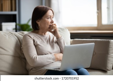 Thoughtful mature woman using laptop, sitting on couch at home alone, pensive older female thinking about finance or health problem, looking in distance, having doubts, feeling lonely