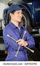 Thoughtful Mechanic Holding Rim Wrench At Garage
