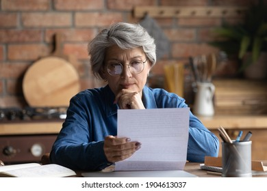 Thoughtful middle aged 60s woman in eyeglasses reading paper letter carefully. Pensive focused older mature retired lady looking at correspondence sheet. considering bank notification at home.