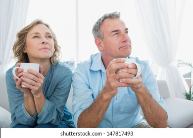 Thoughtful middle aged couple sitting on the couch having coffee looking away at home in the living room