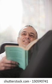 Thoughtful middle aged man with book relaxing at home