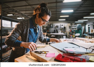 Thoughtful middle-aged industrial female engineer with eyeglasses working with a tape measure in the workshop.