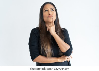Thoughtful middle-aged woman touching chin. Attractive lady looking upwards. Contemplation concept. Isolated front view on white background.