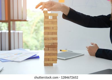Thoughtful and mindful business woman playing wooden block tower in office. Risk and strategy business concept.