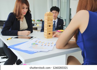 Thoughtful and mindful group of business people playing wooden block tower  in office. Risk and strategy business concept.