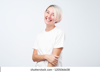 Thoughtful model with short dyed hair dressed in white t-shirt standing in studio. Her hand near the face. Isolated on gray background
