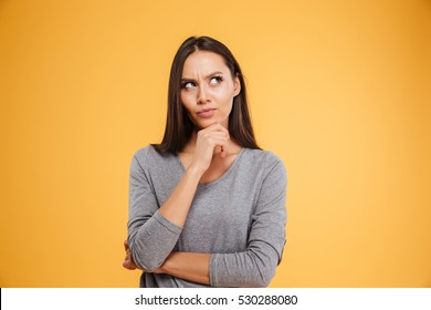 Thoughtful model in studio looking away. hand near the face. isolated orang background