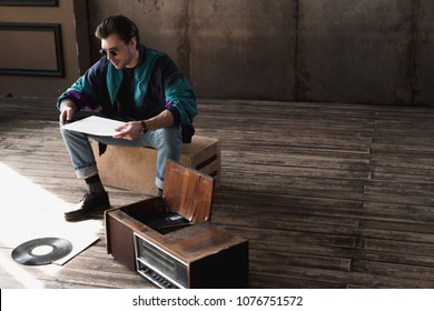 thoughtful nostalgic man in vintage windcheater with vinyl record player