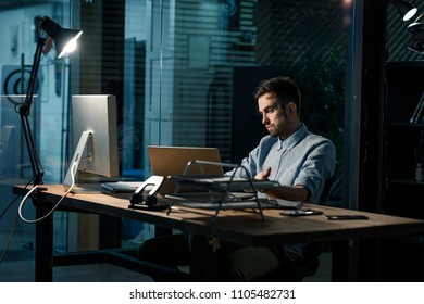 Thoughtful office working man sitting at computer at night.