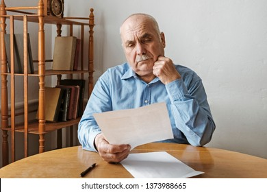 Thoughtful old man reading a handheld paper document with a look of concentration as he sits indoors at a table