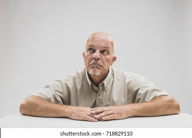 Thoughtful older balding man sitting at a table looking up into the air with a contemplative expression as he makes plans or reminisces old memories
