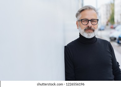 Thoughtful older man leaning on a receding exterior wall in an urban street looking intently at the camera