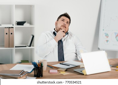 thoughtful overweight businessman working with notepad and laptop in office