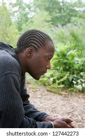 Thoughtful, pensive African American man sitting thoughtfully outside in nature, with trees in the background