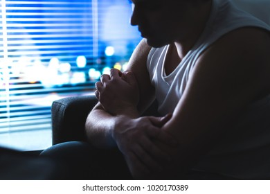 Thoughtful, pensive and contemplating man thinking in dark home at night by the window. Emotional and dramatic mood. Making hard decision. Despair, loneliness or insomnia concept. Young rebel.