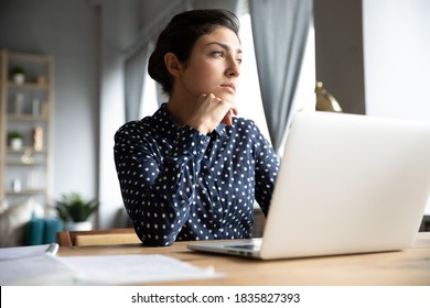 Thoughtful pensive Indian unmotivated employee sit at workplace desk distracted from computer work ponder look out the window feel tired after long workday. Business vision, lack of motivation concept