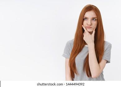 Thoughtful perplexed pondering young redhead blue-eyed woman smirking touching jawline thinking look upper left corner hesitant have doubts, standing white background unsure