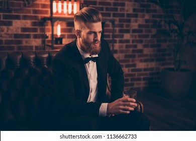 Thoughtful pondering pensive brutal virile masculine focused dream dreamy rich millionaire having a rest on leather divan drinking expensive alcohol beverage modern brunette haircut dress-code chic