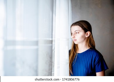 Thoughtful pretty Girl looking out Window.Pensive Teenage girl by the curtain,looking outside.Beautiful portrait of young woman alone at home