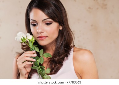 Thoughtful pretty young woman holding a white rose